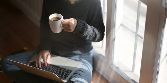 woman-using-laptop-while-holding-a-cup-of-coffee-3759083.jpg
